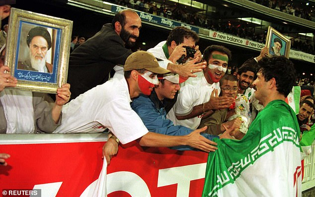 Daei pictured celebrating with Iranian supporters after qualifying for the 1998 World Cup. Around him, fans hold up pictures of the Supreme Leader, Ayatollah Khameini. Iran were drawn against the United States at the tournament, in a game that was billed 'the most politically charged match in World Cup history'